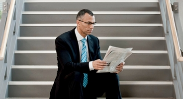 Snapshot of businessman sitting on a staircase reading a newspaper.